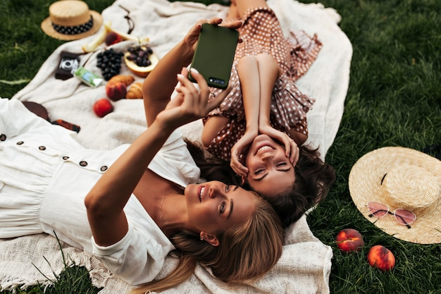 Młode piękne brunetki i blondynki w stylowych letnich sukienkach szczerze się uśmiechają, robią sobie selfie i urządzają piknik na zewnątrz