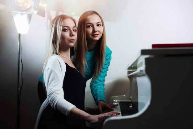Młode piękne dziewczyny gry na pianinie.