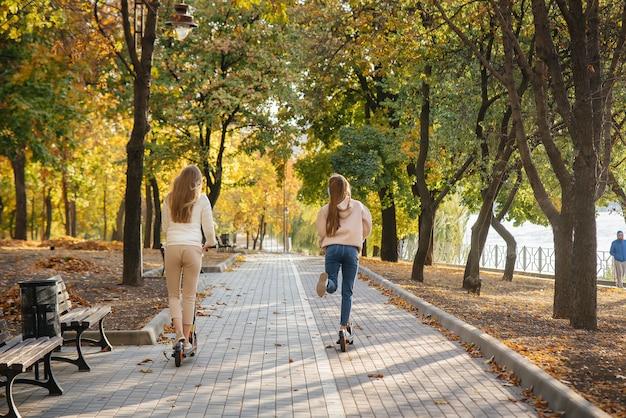 Młode piękne dziewczyny jeżdżą po parku na skuterze elektrycznym w ciepły jesienny dzień. spacerować w parku.