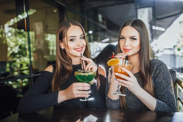 Młode piękne dziewczyny siedzą na letnim tarasie nowoczesnej kawiarni i piją orzeźwiające koktajle w kolorze pomarańczowym i zielonym.