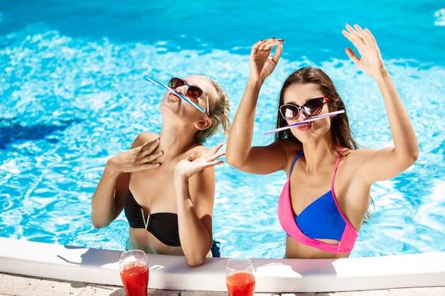 Młode piękne dziewczyny uśmiechają się, wygłupiają, mówią, relaksują się w basenie.