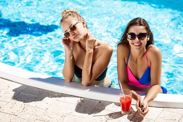 Młode piękne dziewczyny uśmiechnięte, mówiące, relaks w basenie.