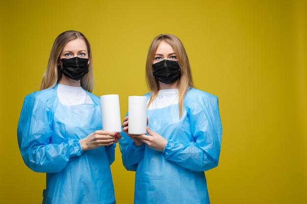Młode piękne dziewczyny w jednorazowych fartuchach medycznych i maskach na twarzach trzymają mokre chusteczki antybakteryjne, portret odizolowany na żółtym tle