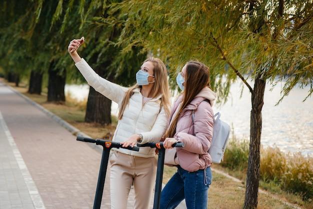Młode piękne dziewczyny w maskach jeżdżą po parku na hulajnodze elektrycznej w ciepły jesienny dzień i robią selfie. spacerować w parku.