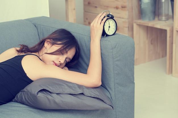 Młode piękne kobiety śpią na kanapie dotykając zegara