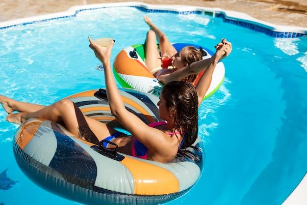 Młode piękne kobiety uśmiechnięte, opalanie, relaks, pływanie w basenie