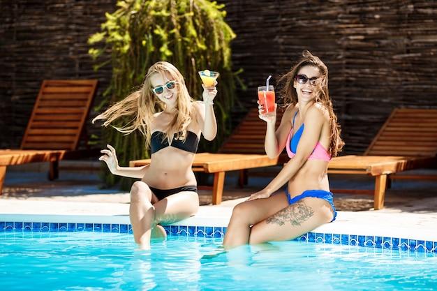 Młode piękne kobiety uśmiechnięte, opalanie, relaks w pobliżu basenu