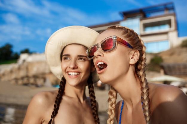 Młode piękne kobiety w strojach kąpielowych radujące się, uśmiechnięte, śmiejące się z morza