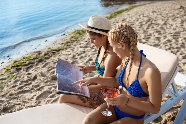 Młode piękne kobiety w strojach kąpielowych, uśmiechając się, przeglądaj magazyn nad morzem
