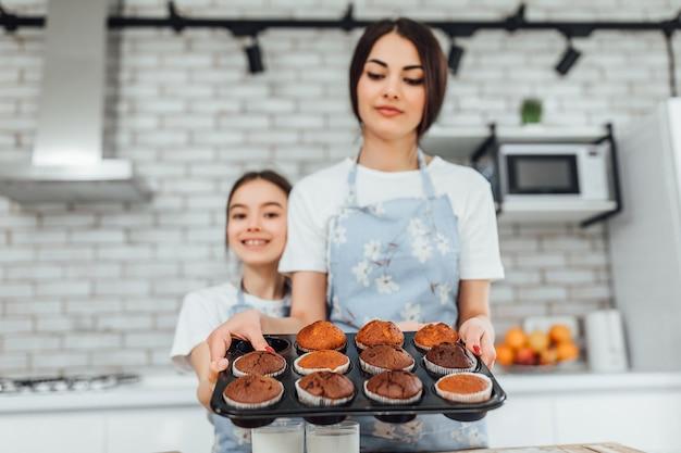 Młode piękne siostry gotują babeczki