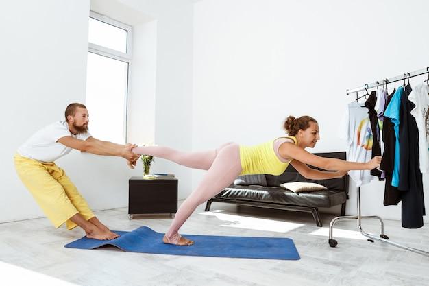 Młode piękne sportive pary partnera szkolenia jogi asany w domu.
