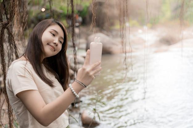 Młode piękne szczęśliwe azjatyckie dziewczyny one uśmiechają się podczas gdy ona selfie z smartphone mobilną pobliską siklawą.
