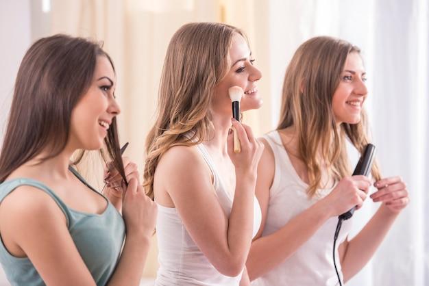 Młode piękno dziewczyny robią makijażowi i robią włosy.