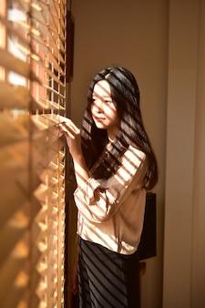 Młode piękno kobiety stoi przy okno