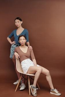 Młode poważne brunetki bliźniaczki w casual, patrzące na ciebie, podczas gdy jedna z nich siedzi na białym plastikowym krześle w studio z brązowymi ścianami
