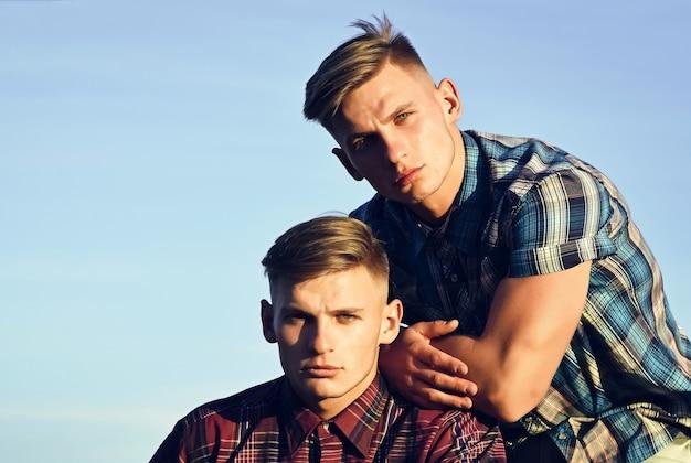 Młode przystojne bliźniaki pozują z poważną miną