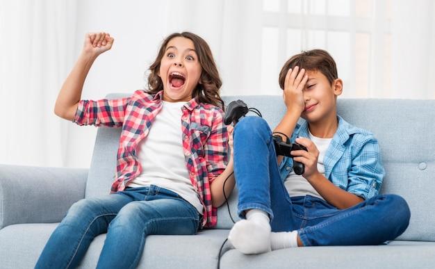 Młode rodzeństwo bawi się joystickiem