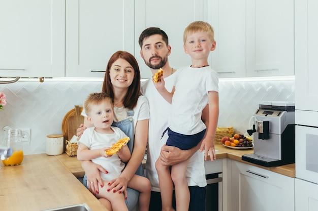 Młode rodziny przygotowujące razem śniadanie, mąż, kobieta i dwoje dzieci