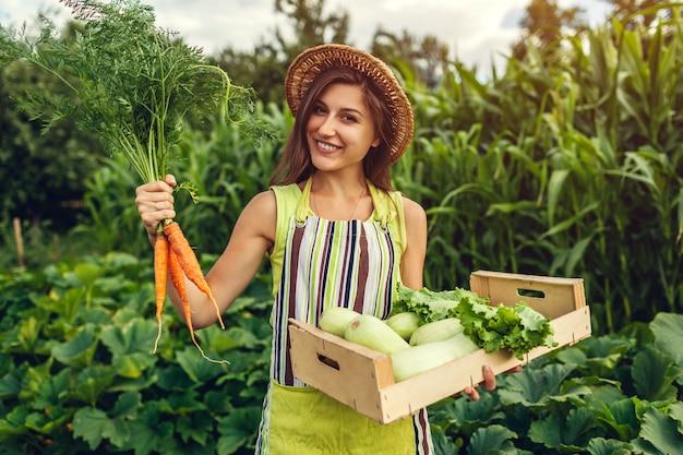 Młode rolnik gospodarstwa marchewki i drewniane pudełko wypełnione świeżymi warzywami. kobieta zebrała letnie plony. prace ogrodowe