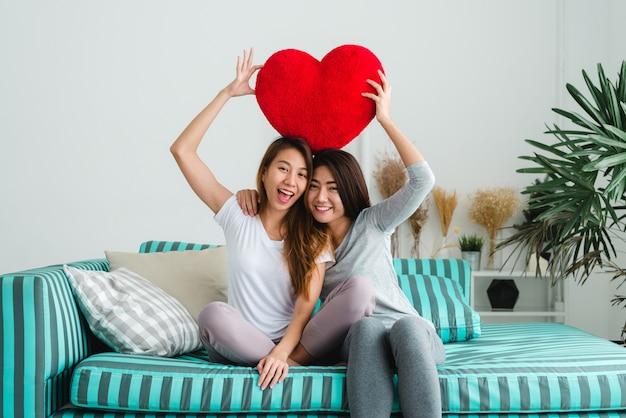 Młode śliczne azjatykcie lesbijki trzyma czerwonego kierowego kształta wierzbowego wpólnie ono uśmiecha się z szczęściem w domu