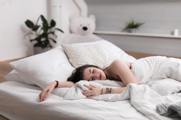 Młode śliczne kędzierzawe kobiety kłaść w jej łóżku i ono uśmiecha się w jej sen. niskie łóżko materacowe układa się bezpośrednio na drewnianej podłodze