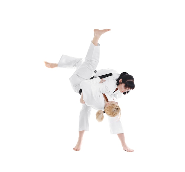 Młode sportowe kobiety ćwiczące sztuki walki na białym tle