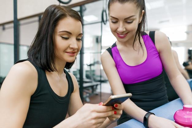 Młode sportowe kobiety w siłowni mówią uśmiechnięte