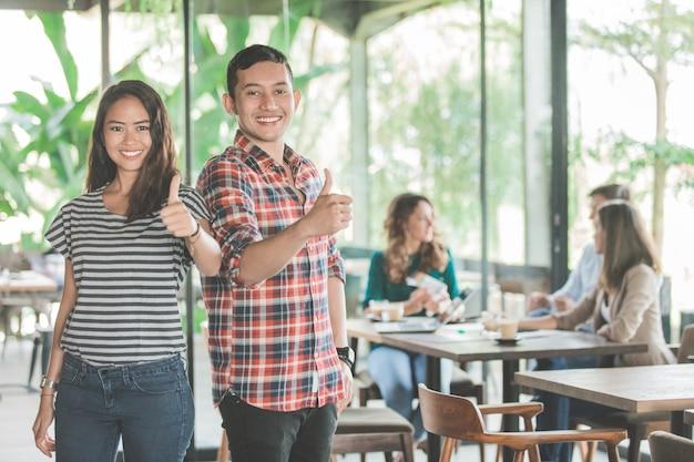 Młode spotkanie biznesowe w kawiarni. dwóch partnerów pokazuje kciuk w górę