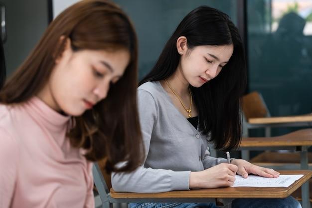 Młode studentki uniwersytetu koncentrują się na egzaminowaniu w klasie. uczennice poważnie pisze ćwiczenia z egzaminów w klasie.