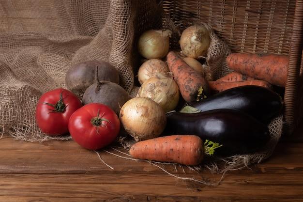 Młode surowe brudne cebule, marchewki, czosnek, oberżyna i świezi pomidory na drewnianym tle