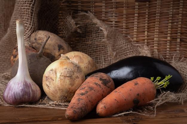 Młode surowe brudne ziemniaki, cebule, marchewki, czosnek i bakłażan na drewnianym tle