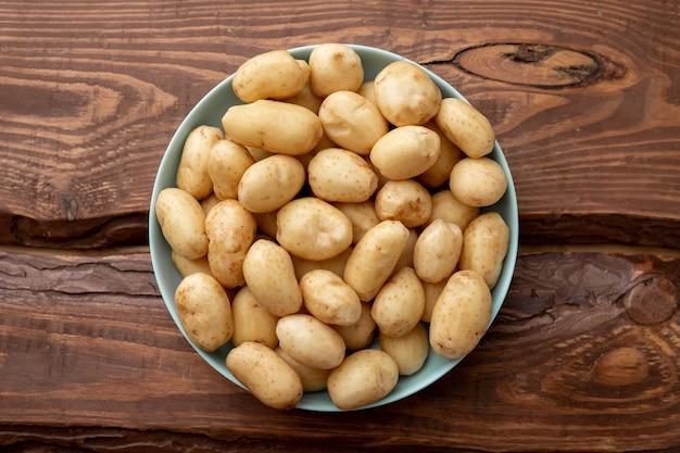 Młode surowe ziemniaki małe na talerzu na brązowym tle drewnianych.
