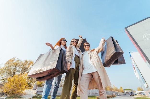 Młode szczęśliwe kobiety chodzą na ulicy z torby na zakupy.