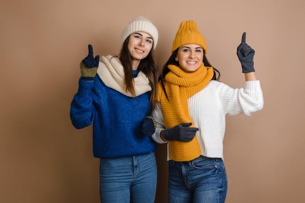 Młode szczęśliwe kobiety gestykulujące za pomocą makijażu palcami, są podekscytowane dobrym pomysłem, zdobywając inspirację.