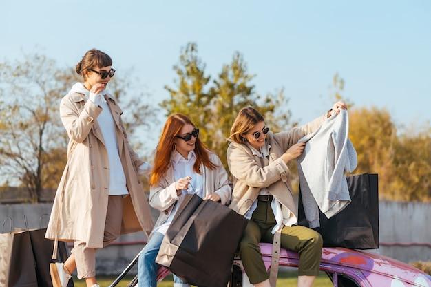 Młode szczęśliwe kobiety z torby na zakupy pozowanie w pobliżu starego zdobionego samochodu