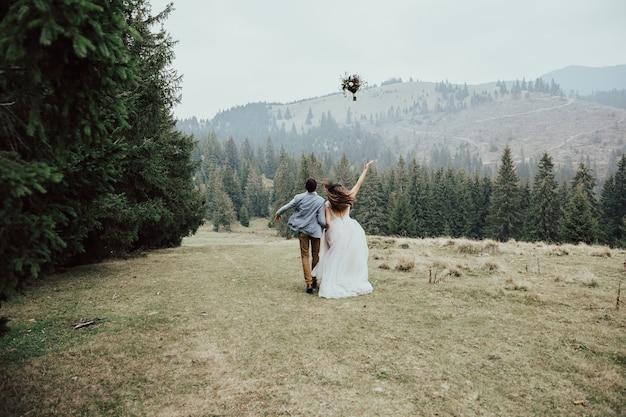 Młode szczęśliwe małżeństwo biegnie w zielonym lesie, rzucając bukiet ślubny.