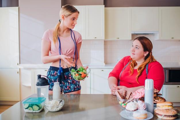 Młode szczupłe i grube kobiety w kuchni patrzą na siebie. dobrze zbudowana modelowa miska z sałatką. spojrzenie na nią z nadwagą. zdrowe i niezdrowe jedzenie na stole.