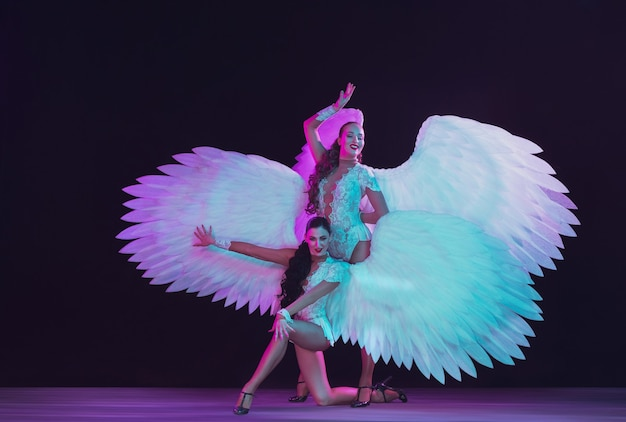 Młode tancerki z białymi anielskimi skrzydłami w neonowych kolorach. zgrabne modele, kobiety tańczące, pozowanie.