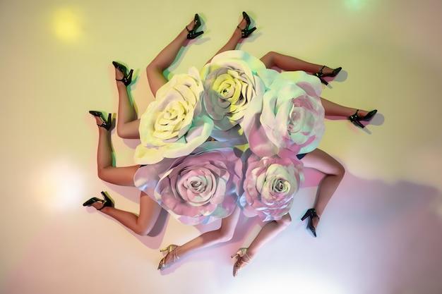Młode tancerki z ogromnymi kwiatowymi kapeluszami w neonowym świetle na ścianie gradientowej