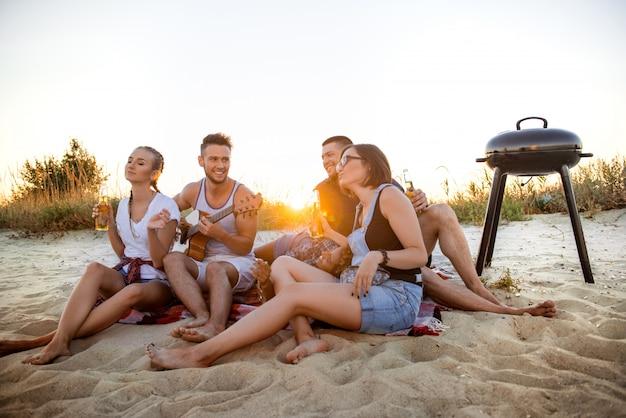 Młode towarzystwo przyjaciół radujących się, odpoczywających na plaży podczas wschodu słońca