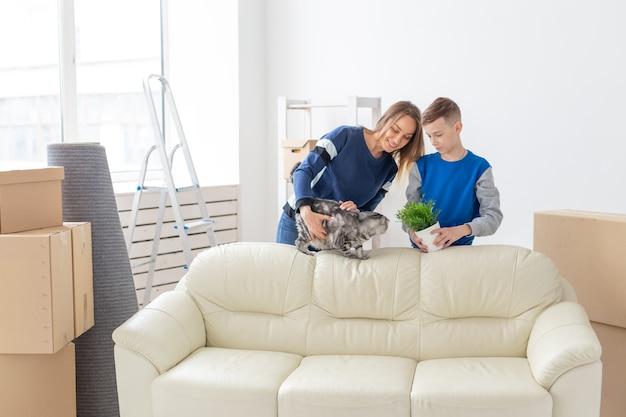 Młode urocze samotne matki i syn są szczęśliwi z przeprowadzki do nowego domu, w których trzymają szkockiego szkockiego
