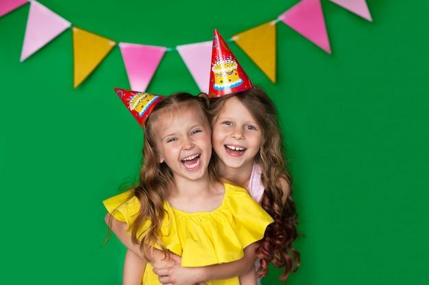 Młode urodzinowe dziewczyny w żółtej bluzce z nakrętką śmia się na zielonym tle z kopii przestrzenią. bardzo szczęśliwy.