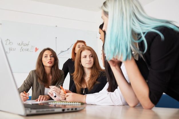 Młode uśmiechnięte biznesowe kobiety pracuje nowego projekt przy biurem.