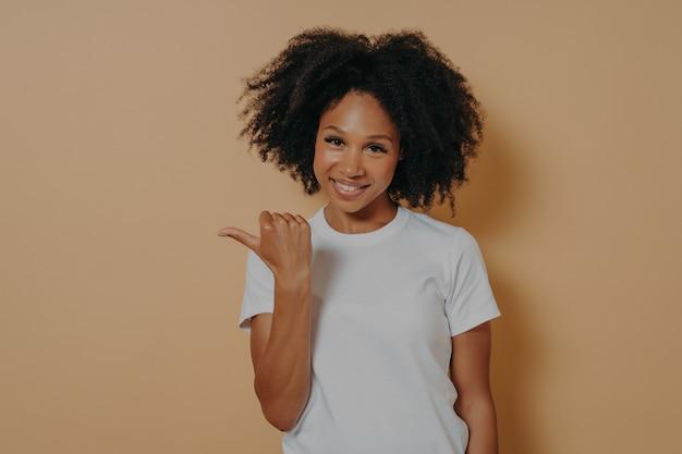 Młode uśmiechnięte, ciemnoskóre kobiece kręcone włosy wskazujące na bok kciukiem, pokazują puste miejsce na promocję lub reklamę z pozytywnym wyrazem twarzy, odizolowane na beżowej ścianie