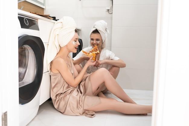 Młode uśmiechnięte kobiety europejskie jedzenie pizzy w łazience. dziewczyny z przepaskami pod oczami na twarzach i zawiniętymi ręcznikami kąpielowymi na głowach. koncepcja strony dziewcząt w domu. wnętrze nowoczesnego mieszkania