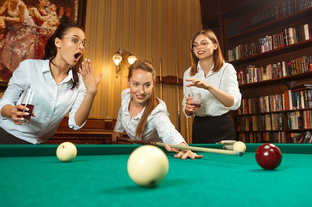 Młode uśmiechnięte kobiety grające w bilard w biurze lub w domu po pracy.