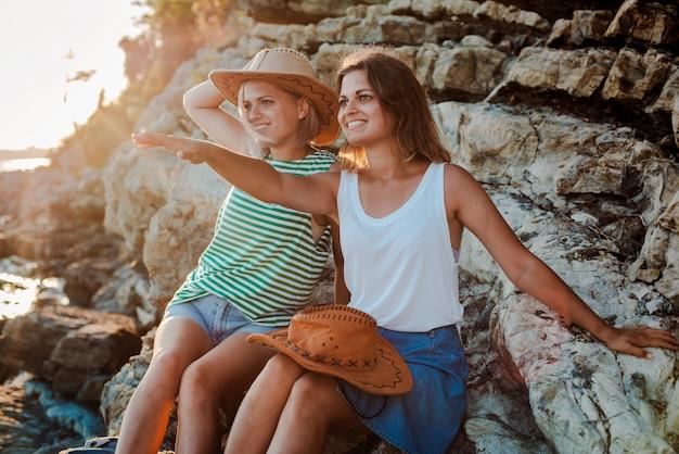 Młode wesołe kobiety w czapkach biodrówki na skale na wybrzeżu morza.