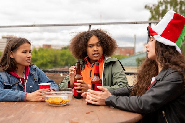 Młode wieloetniczne kibice piłkarskie piją piwo z frytkami podczas omawiania głównych momentów meczu