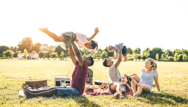 Młode wielorasowe rodziny bawią się z dziećmi na pikniku przy grillu