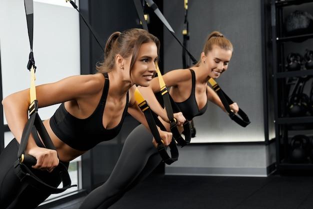 Młode wysportowane kobiety wykonujące ćwiczenia z systemem trx